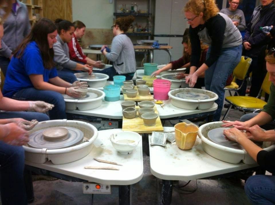 Adults and children working with clay on wheels at a clay throw-athon