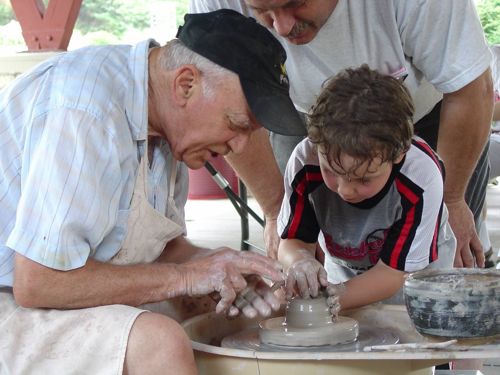 A man and a boy working with a piece of clay on a wheel