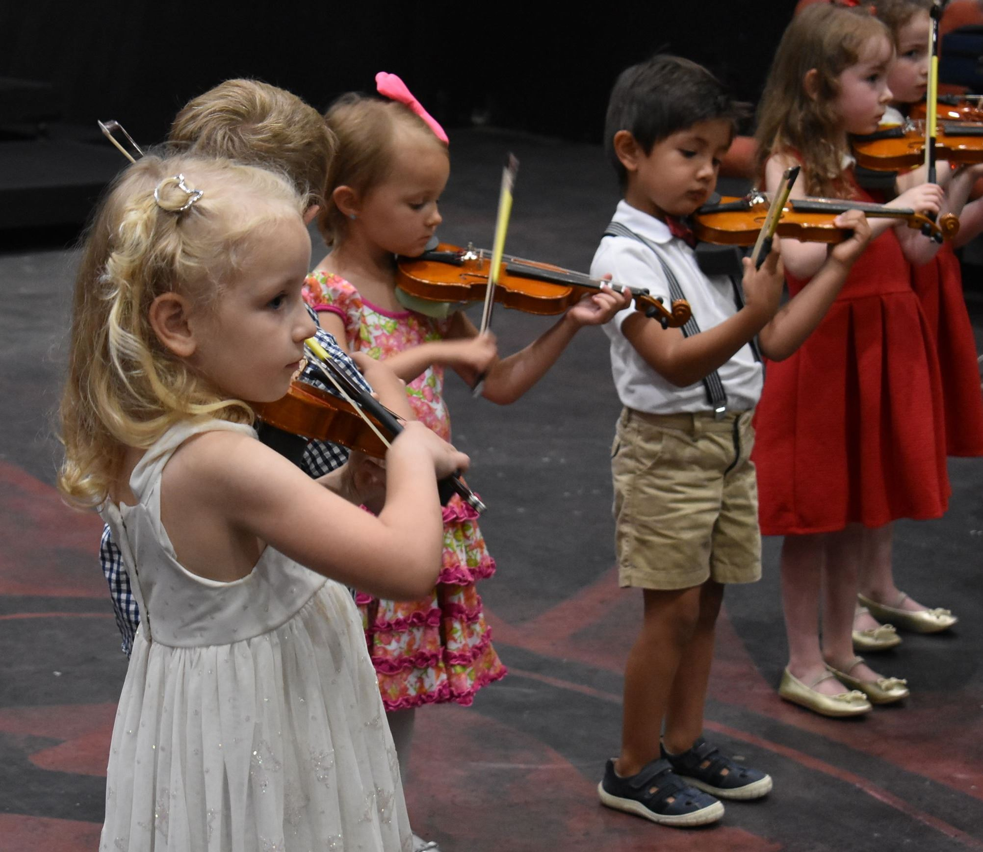 Young children play the violin in our group violin class